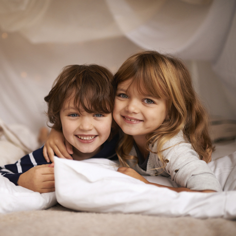 Portrait of two adorable siblings lying on pillows underneath a fort