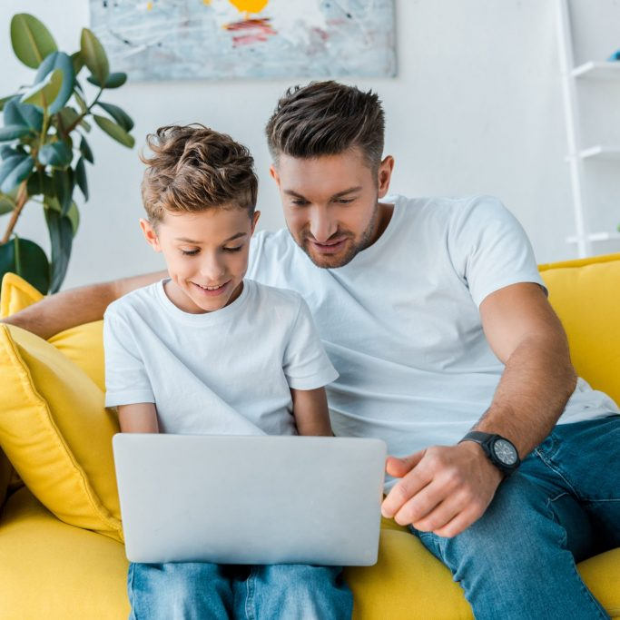 happy father and son looking at laptop at home