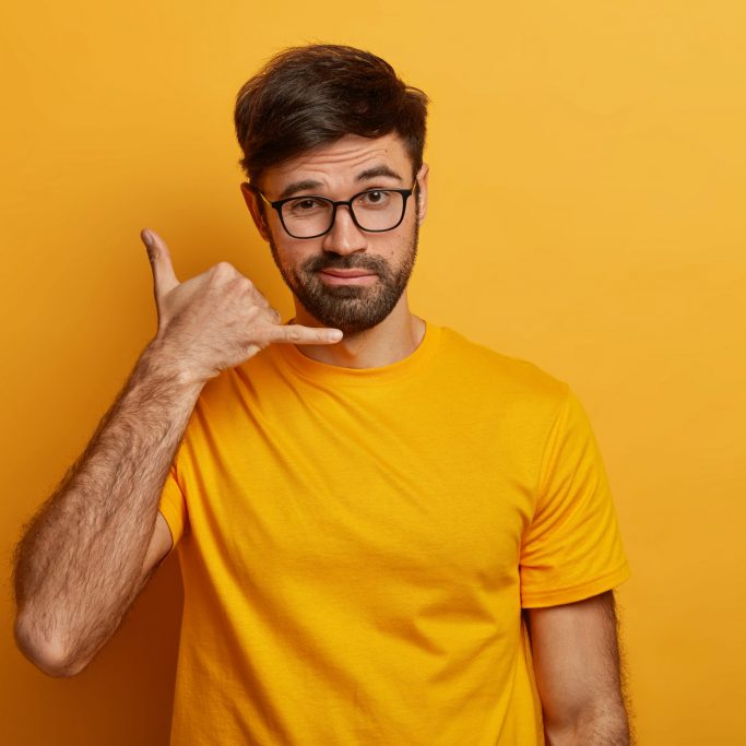 Confident charismatic man makes call me gesture, communicates with gestures, asks girlfriend telephone number, looks with flirty expression, isolated on yellow wall, wears casual outfit. Body language